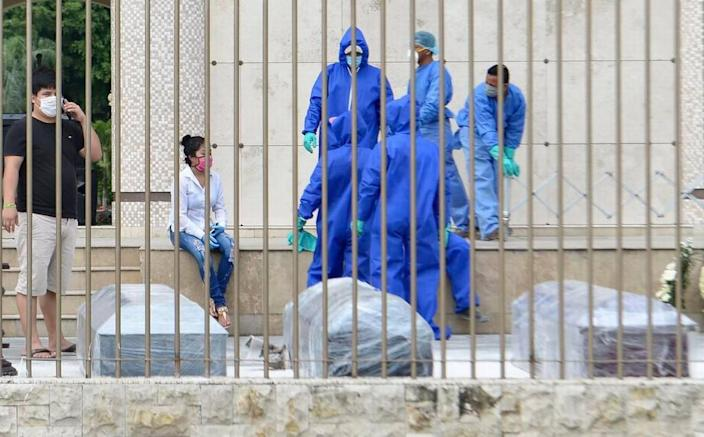 Cemetery workers in Guayaquil, Ecuador, wait to burry people who died from COVID-19 in April 2020. Their coffins were wrapped in plastic.