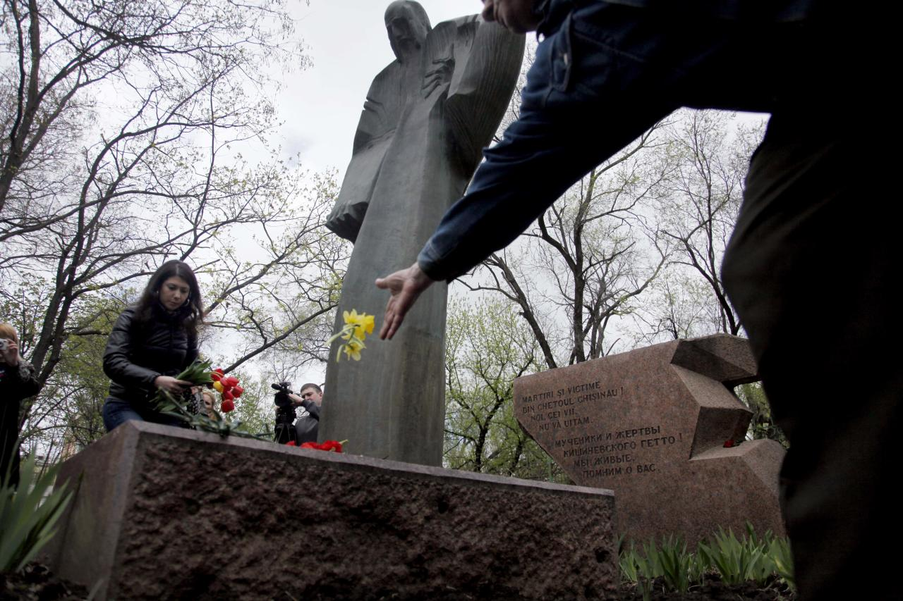 People place flowers at the Holocaust remembrance memorial in Chisinau, Moldova, Thursday April 19, 2012. March 19 marks the day of remembrance for the lives of 6 million Jews claimed in the Holocaust during World War II. (AP Photo/John McConnico)