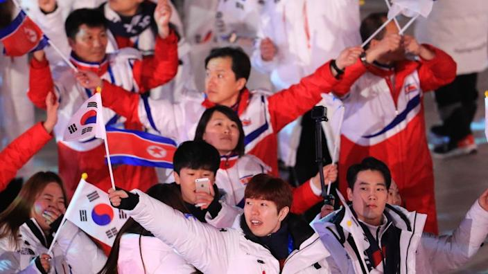 Delegations from North Korea and South Korea march under the Korean unification flag