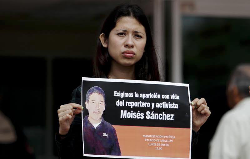 A journalist holds a poster during a protest for the disappearance of journalist Moises Sanchez Cerezo in front of the municipal palace of Medellín de Bravo, Veracruz, Mexico on January 5, 2015
