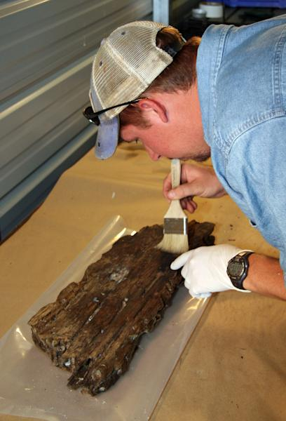 This Aug. 8, 2012, photo shows Chad Gulseth cleaning a piece of wood from the 17th-century French ship La Belle at the Texas A&M University Center for Maritime Archaeology and Conservation in Bryan, Texas. The wood has spent months inside a 40-foot-long, 8-feet-wide freeze dryer being used to remove moisture from the wreckage of the ship used by famed explorer La Salle that sank more than 300 years ago off the Texas coast. (AP Photo/Michael Graczyk)
