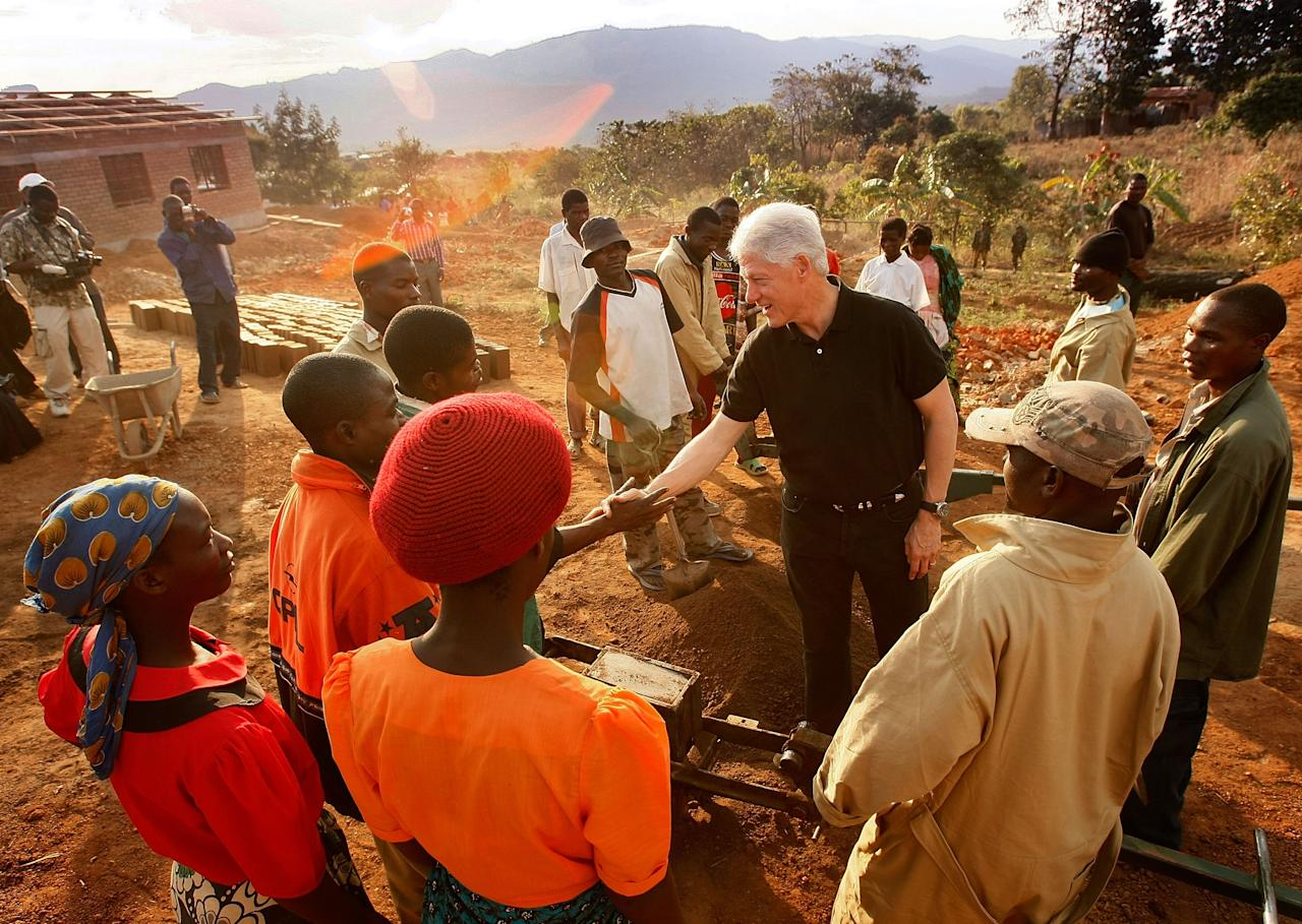 Former President Clinton visits the construction site of a rural hospital on a trip to Malawi in 2007. The rural hospital project is a collaboration between the Clinton Foundation and Partners in Health that aims to increase access to health care in rural communities.<br><br>(Photo credit: Win McNamee/Getty Images for the Clinton Foundation)