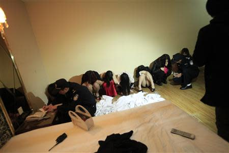 Police write down the details of suspects who were detained during a police raid, as part of plans to crackdown on prostitution, at a hotel in Dongguan, Guangdong province, February 9, 2014. REUTERS/Stringer