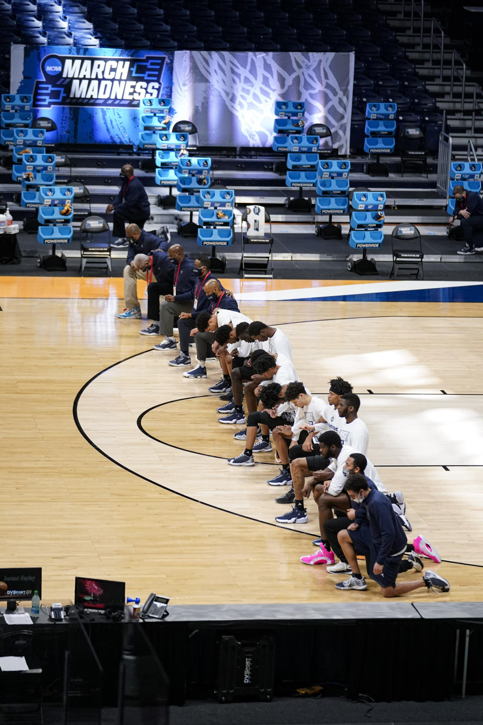 Members of the Georgetown team take a knee during the National Anthem before a first-round game against Colorado in the NCAA men's college basketball tournament at Hinkle Fieldhouse in Indianapolis, Saturday, March 20, 2021. Colorado defeated Georgetown 96-73. Restrictions due to the COVID-19 pandemic have limited crowds, reduced interactions and created an abnormal NCAA experience for those involved. (AP Photo/Michael Conroy)