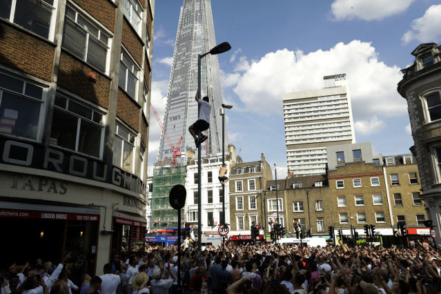 England soccer fans climb lampposts and traffic lights, backdropped by the Shard skyscraper, as they celebrate in the London Bridge area of London after England won their quarterfinal match against Sweden at the 2018 soccer World Cup, Saturday, July 7, 2018. (AP Photo/Matt Dunham)