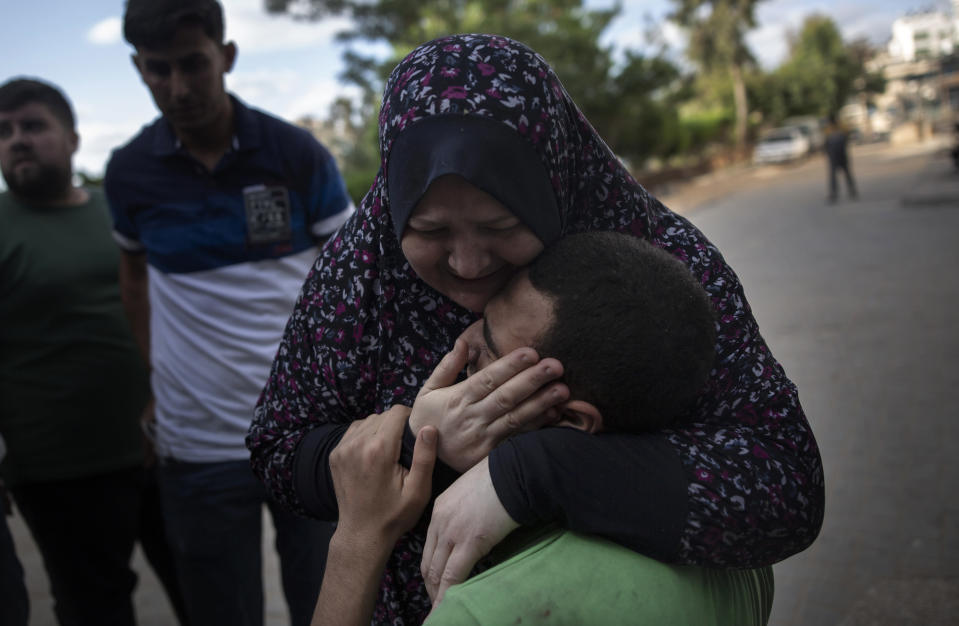 Relatives react to the death of a man who was killed by an Israeli airstrike that destroyed the upper floors of a commercial building and caused damage to the nearby Health Ministry and prime health care clinic, in Gaza City, Monday, May 17, 2021. (AP Photo/Khalil Hamra)