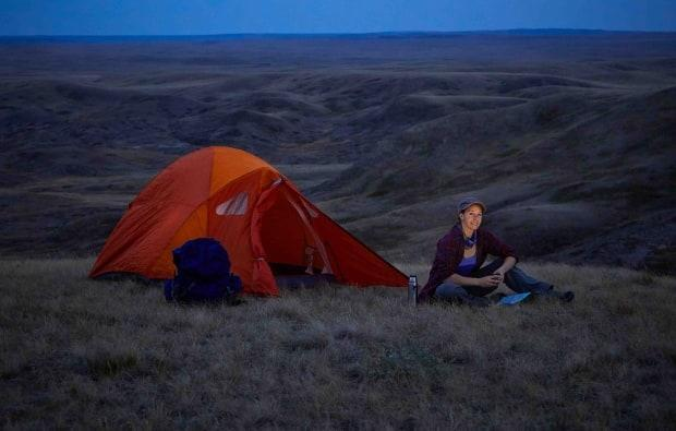 A camper sits by their tent at Grasslands National Park. (Parks Canada Service - image credit)