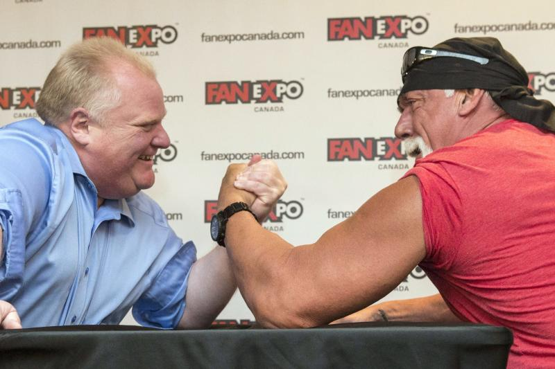 Toronto City Mayor Rob Ford, left, takes on professional wrestler Hulk Hogan in an arm-wrestling match to promote Fan Expo in Toronto on Friday, Aug. 23, 2013 . (AP Photo/The Canadian Press, Chris Young)