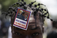 A supporter of former Haitian President Jean-Bertrand Aristide wears a photo of Aristide and late South African President Nelson Mandela as he waits near the airport others for Aristide's expected arrival from Cuba, where he underwent medical treatment in Port-au-Prince, Haiti, Friday, July 16, 2021. Aristide's return adds a potentially volatile element to an already tense situation in a country facing a power vacuum following the July 7 assassination of President Jovenel Moïse. (AP Photo/Joseph Odelyn)
