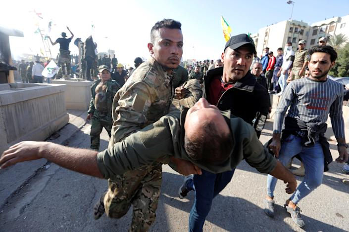 A wounded member of Hashd al-Shaabi (paramilitary forces) gets help during a protest to condemn air strikes on their bases, outside the main gate of the U.S. Embassy in Baghdad, Iraq December 31, 2019. (Photo: Khalid al-Mousily/Reuters)