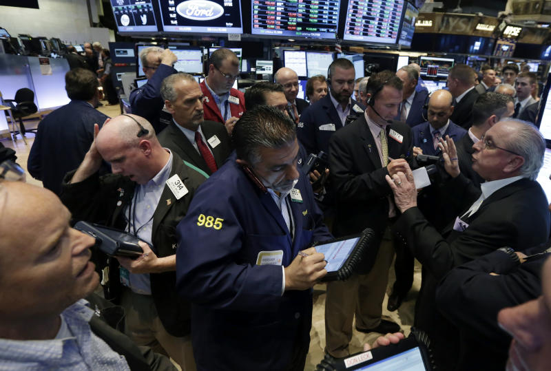Nicholas Brigandi, right, managing director of NYSE floor operations, works with traders at the post that handles Enservco Corp., on the floor of the New York Stock Exchange, Friday, June 20, 2014. Stocks held on to small gains, enough to mark the latest record high closes for major indexes. (AP Photo/Richard Drew)