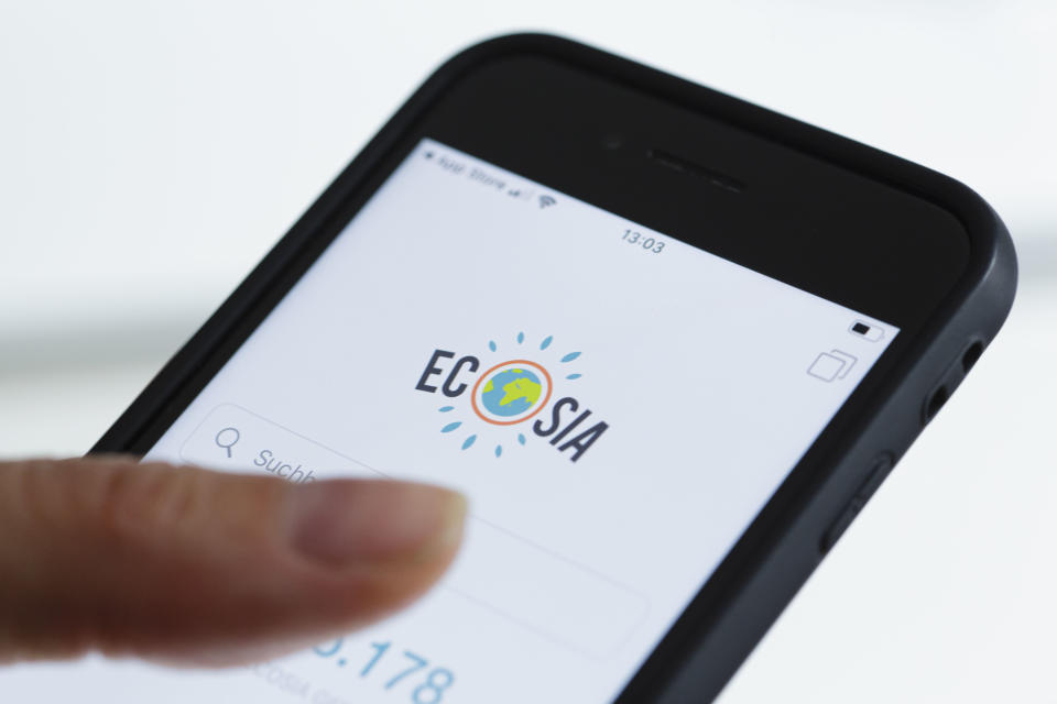 BERLIN, GERMANY - OCTOBER 22: In this photo illustration the logo of search engine Ecosia is displayed on a smartphone on October 22, 2019 in Berlin, Germany. Ecosia donates 80% or more of its profits to nonprofit organizations that focus on reforestation (Photo Illustration by Thomas Trutschel/Photothek via Getty Images)
