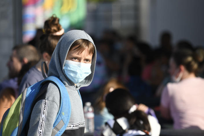A masked student waits before the bell at Enrique S. Camarena Elementary School, Wednesday, July 21, 2021, in Chula Vista, Calif. The school is among the first in the state to start the 2021-22 school year with full-day, in-person learning. (AP Photo/Denis Poroy)