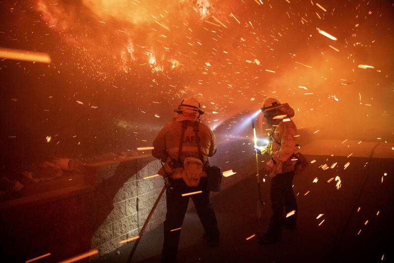 In this Thursday, Oct. 10, 2019 photo, embers from the Saddleridge fire blow by firefighters in Sylmar, Calif. (Photo: Michael Owen Baker/AP)
