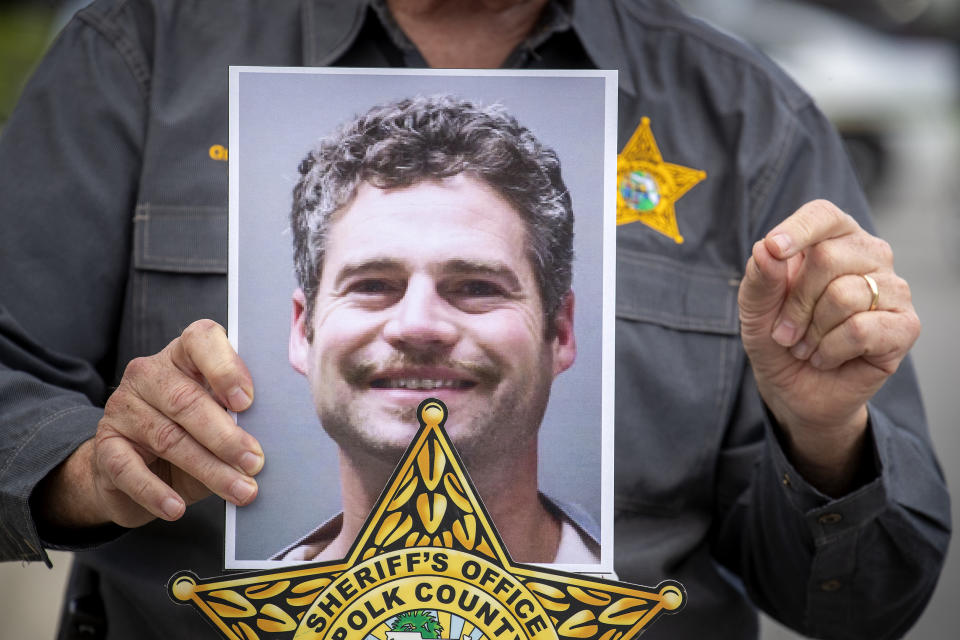 Shaun Runyon's picture held up by a representative of the Polk County Sheriff's Office. Source: The Ledger via AP