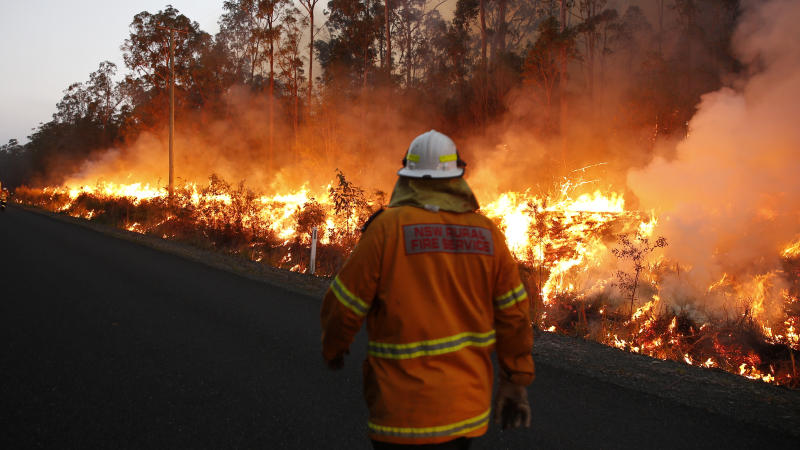 An RFS crewman watches a back burn along Aerodrome road, Nabiac , Sunday, October 27, 2019. Almost 1200 firefighters are tackling large bushfires on the NSW mid-north coast among scores of blazes around the state. (AAP Image/Darren Pateman) NO ARCHIVING