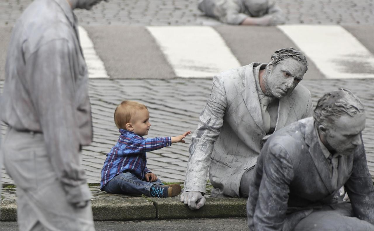 <p>A small boy touches a participants of the performance '1000 GESTALTEN' with hundreds of people painted like clay figures moving slowly and silently through the streets of Hamburg to protest against the G-20 summit in Hamburg, northern Germany, July 5, 2017. (Matthias Schrader/AP) </p>