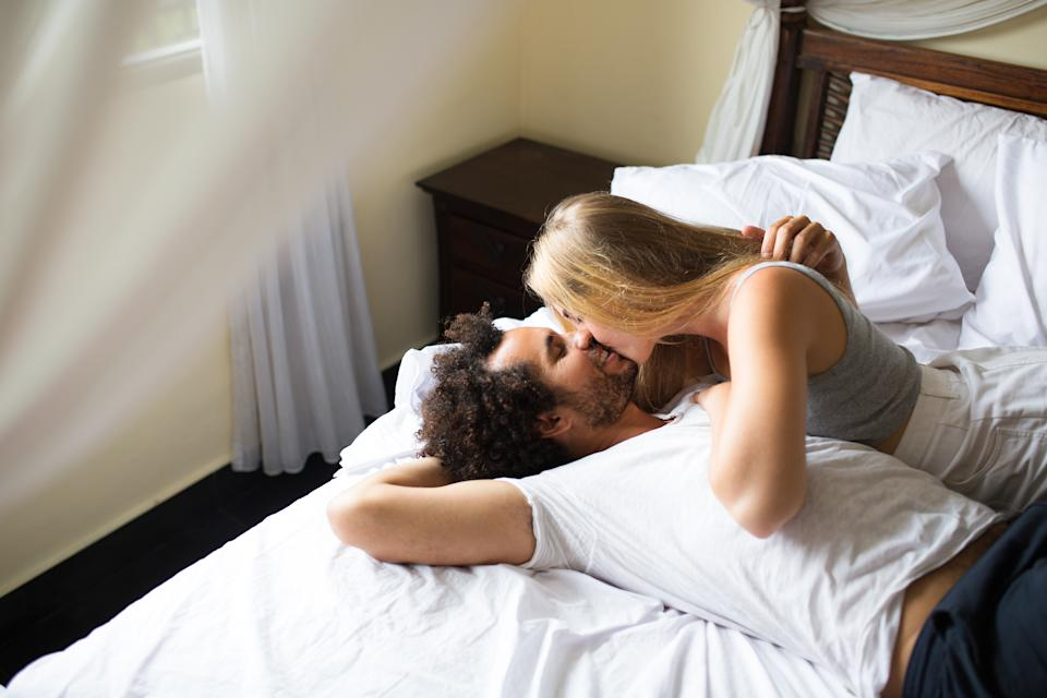 [Note for inspector: Photo files for execlusive account] Affectionate young couple kissing in bed. Passionate couple enjoying vacation in suite. They lying in four poster bed and relaxing. Sexual attraction concept