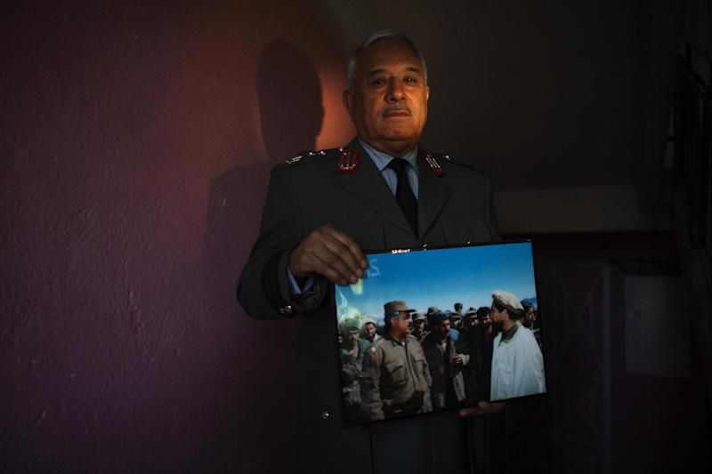 In this Tuesday, Oct. 2, 2012 photo, Gen. Majid Rouzi, a former civil war commander who now is an adviser to the Ministry of Interior, poses with his favorite civil war photograph which shows Gen. Rouzi with one of the best known Afghan military leaders, Ahmad Shah Massoud, in Kabul, Afghanistan. (AP Photo/Dusan Vranic)