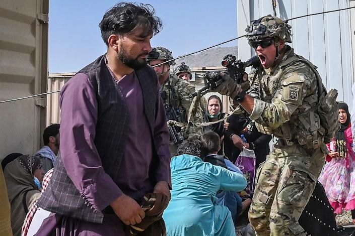 A U.S. soldier points his gun towards an Afghan passenger at the airport in Kabul, Afghanistan, on Monday. (Photo by Wakil Koshar/AFP via Getty Images)
