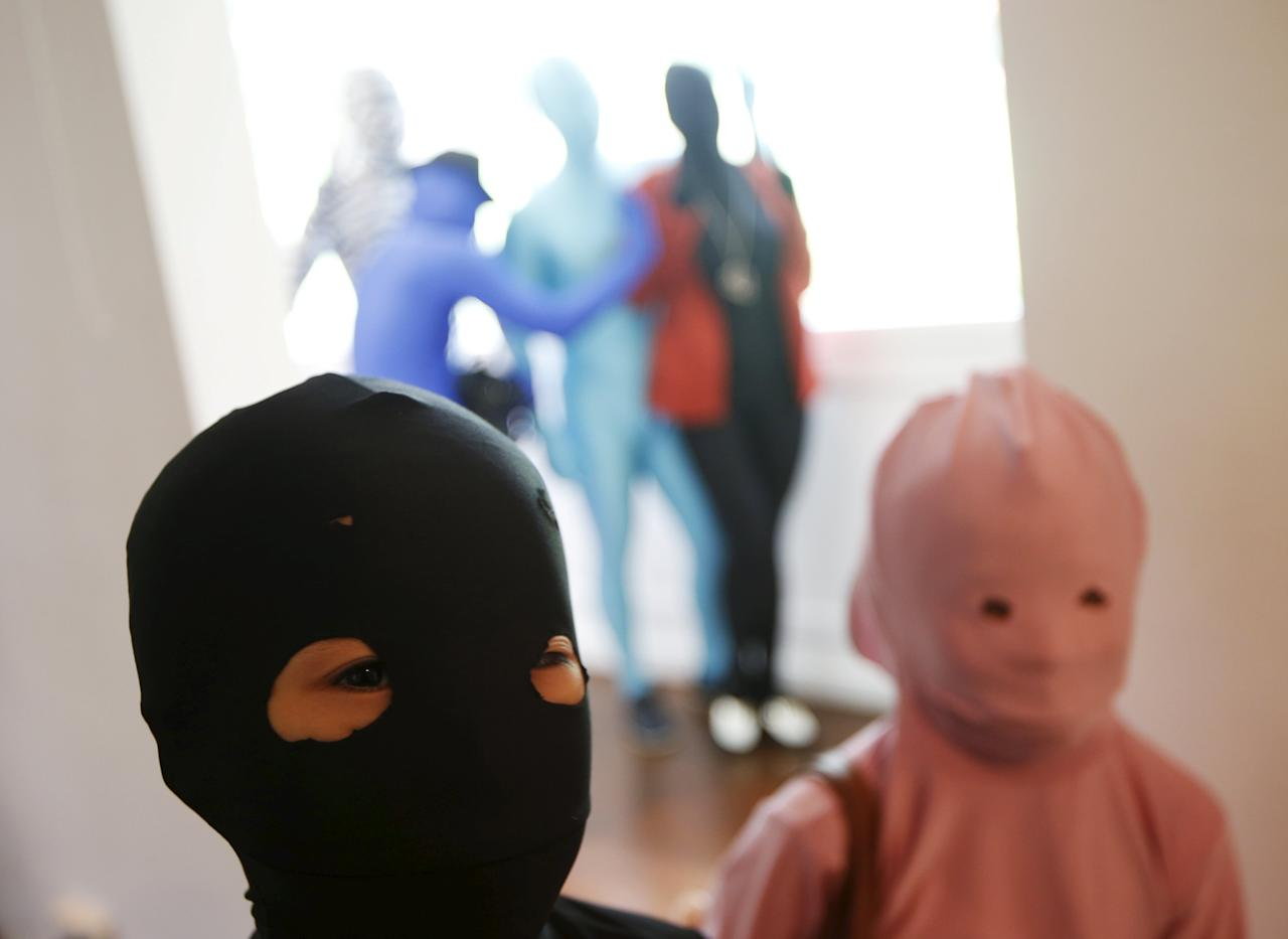 Masaru Morisako (L), a nine-year-old Japanese boy, poses for photos with another child participant in Zentai costumes, or skin-tight bodysuits from head to toe, before a march down the shopping district of Orchard Road during Zentai Art Festival in Singapore May 23, 2015. Close to 50 participants strutted down the busy shopping district during the Zentai art festival which is jointly organized by the Japanese embassy. The festival includes performances and discussions on Zentai from May 22 to from June 5. REUTERS/Edgar Su