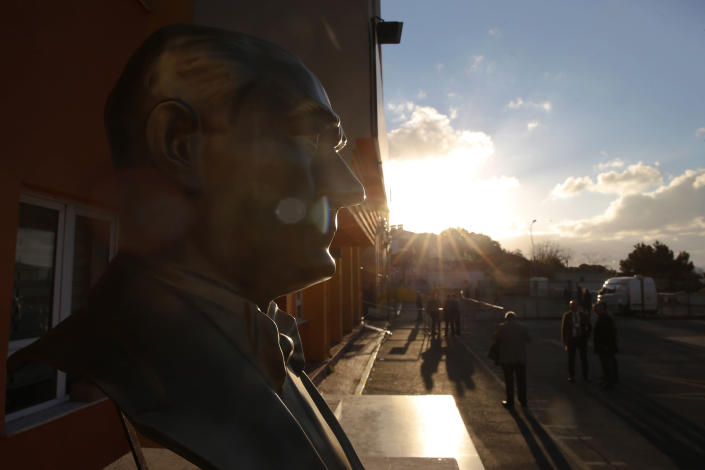 A statue of Turkish Republic founder Mustafa Kemal Ataturk is seen outside of a polling station as voters walk towards to cast they vote in Istanbul, Sunday, March 31, 2019. Turkish citizens have begun casting votes in municipal elections for mayors, local assembly representatives and neighborhood or village administrators that are seen as a barometer of Erdogan's popularity amid a sharp economic downturn. (AP Photo/Lefteris Pitarakis)
