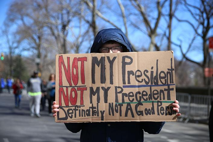 """<p>A demonstrator holds up signs during the """"Not My President's Day"""" rally at Central Park West in New York City on Feb. 20, 2017. (Gordon Donovan/Yahoo News) </p>"""