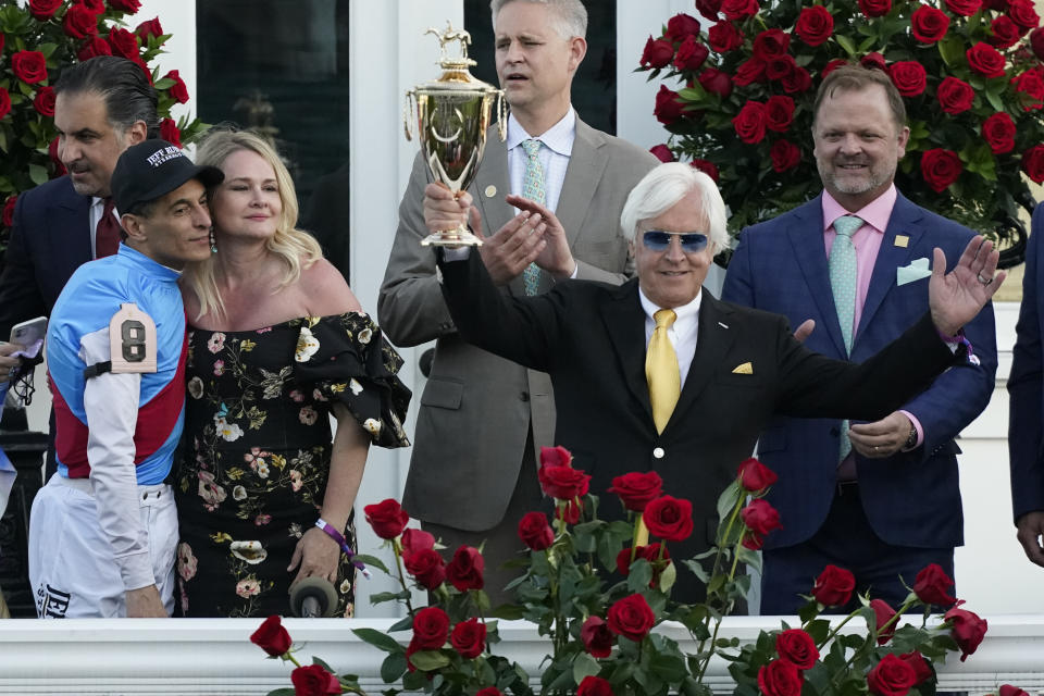 Jockey John Velazquez, left, watches as trainer Bob Baffert holds up the winner's trophy after they victory with Medina Spirit in the 147th running of the Kentucky Derby at Churchill Downs, Saturday, May 1, 2021, in Louisville, Ky. (AP Photo/Jeff Roberson)