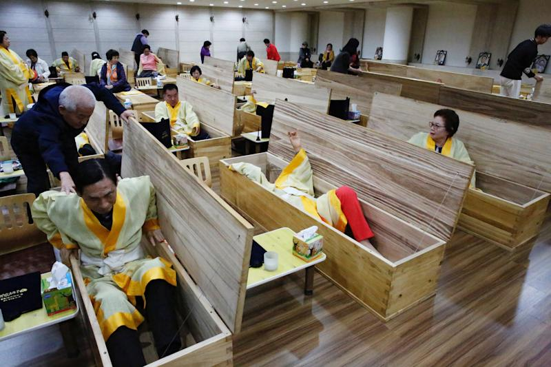 """Participants get into coffins during a """"living funeral"""" event as part of a """"dying well"""" programme, in Seoul, South Korea, October 31, 2019. Picture taken on October 31, 2019. REUTERS/Heo Ran"""