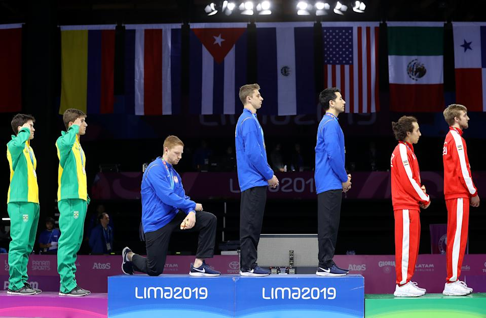 LIMA, PERU - AUGUST 09: Gold medalist Race Imboden of United States  takes a knee during the National Anthem Ceremony in the podium of Fencing Men's Foil Team Gold Medal Match Match on Day 14 of Lima 2019 Pan American Games at Fencing Pavilion of Lima Convention Center on August 09, 2019 in Lima, Peru. (Photo by Leonardo Fernandez/Getty Images)