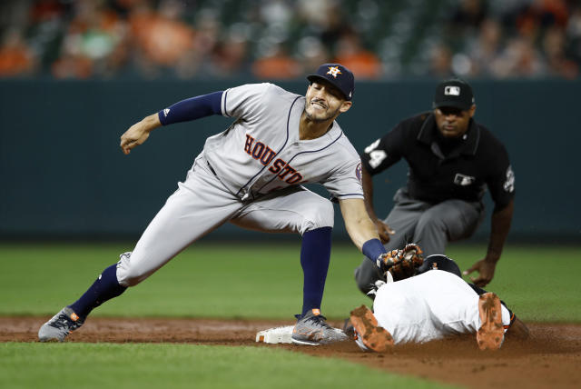 Houston Astros shortstop Carlos Correa, left, tags out Baltimore Orioles' Cedric Mullins as Mullins attempts to steal second base in the third inning of a baseball game, Friday, Sept. 28, 2018, in Baltimore. (AP Photo/Patrick Semansky)