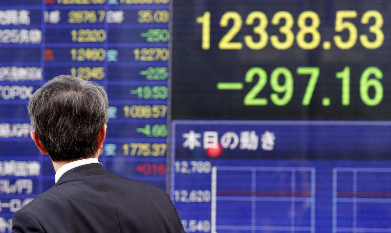A man looks at an electric stock index display of a securities firm in Tokyo, Friday, March 22, 2013.  Japanese stocks tumbled Friday as investors were disappointed by a lack of specifics from the new central bank chief on boosting the economy while other Asian markets fluctuated because of uncertainty over Cyprus' troubled bank restructuring. (AP Photo/Koji Sasahara)
