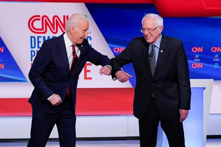 Former Vice President Joe Biden, left, and Sen. Bernie Sanders, I-Vt., right, greet one another by bumping elbows before they participate in a Democratic presidential primary debate at CNN Studios in Washington on March 15, 2020.