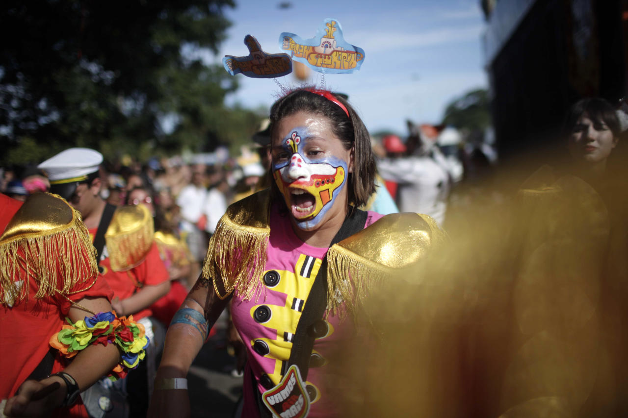 "A reveler, her face painted with the iconic Beatles' Yellow Submarine, participates in the Beatles-themed street party, ""Sargento Pimenta,"" Portuguese for ""Sergeant Pepper,"" at the Aterro do Flamengo urban park in Rio de Janeiro, Brazil, Monday Feb. 20, 2012. The group that organizes the party gives the Beatles repertoire a Brazilian tweak, adapting ""All My Loving"" to the peppy beat of a traditional Carnival ""marchinha,"" or march, and infusing ""Hard Day's Night"" with a Rio funk sound. (AP Photo/Dado Galdieri)"