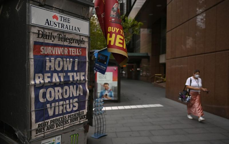 A newspaper headline about the coronavirus outbreak is seen on a near-deserted street in Sydney.