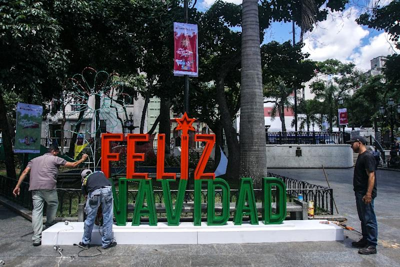 Men work on the installation of a sign wishing merry Christmas in Caracas on November 2, 2017. Credit-rating agencies are increasingly warning of the risk of a Venezuelan debt default (AFP Photo/JUAN BARRETO)