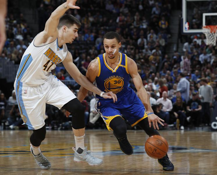 Golden State Warriors guard Stephen Curry, right, drives past Denver Nuggets forward Juancho Hernangomez, of Spain, to the rim in the first half of an NBA basketball game, Monday, Feb. 13, 201, in Denver. (AP Photo/David Zalubowski)