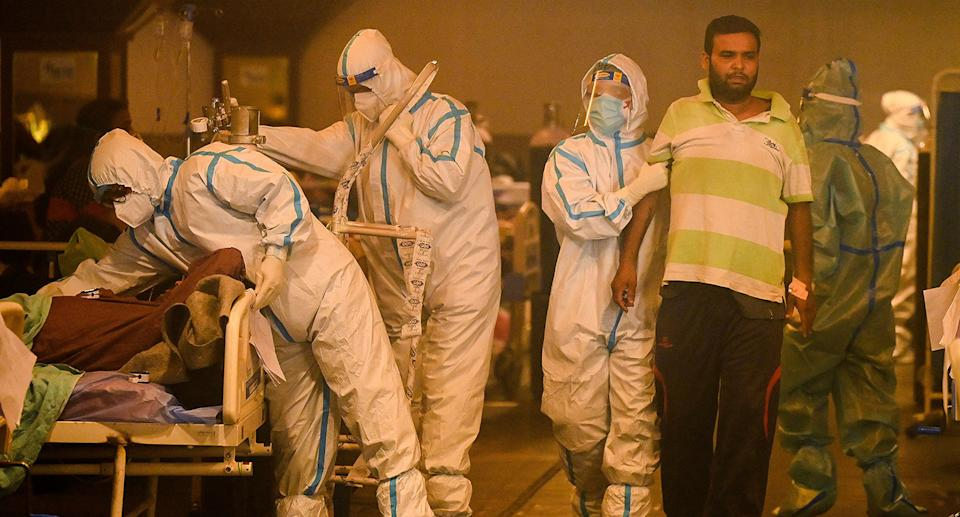 Health workers wearing personal protective equipment (PPE kit) attends to Covid-19 coronavirus positive patients inside a banquet hall temporarily converted into a covid care centre in New Delhi on April 28, 2021. (Photo by Prakash SINGH / AFP) (Photo by PRAKASH SINGH/AFP via Getty Images)