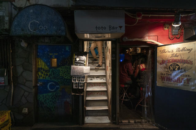 A man pauses briefly while walking down a narrow staircase of a bar in Golden Gai, a bar district in the Shinjuku neighborhood of Tokyo, June 1, 2019, where more than 200 bars are crammed into narrow alleyways. (AP Photo/Jae C. Hong)