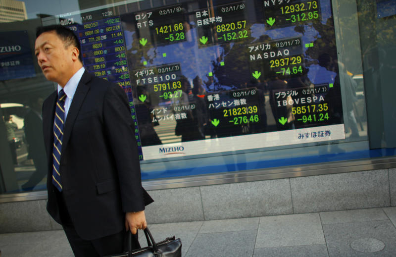 A man stands outside a securities firm in Tokyo Thursday, Nov. 8, 2012. Asian stock markets tumbled Thursday after a ratings agency threatened to downgrade the U.S. if a solution to the so-called fiscal cliff isn't negotiated among lawmakers and newly re-elected President Barack Obama. Japan's Nikkei 225 index shed 1.7 percent to 8,822.15. (AP Photo/Junji Kurokawa)