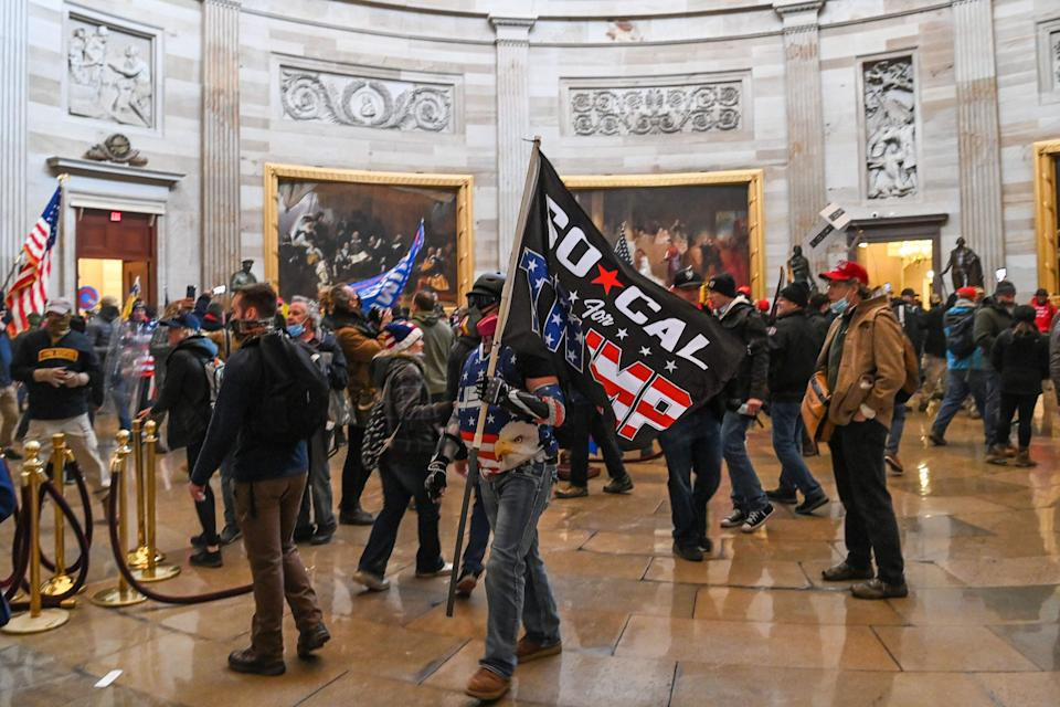 Pro-Trump rioters roam under the Capitol Rotunda after invading the Capitol building on Jan. 6, 2021, in Washington, DC. Demonstrators breached security and entered the Capitol as Congress debated the 2020 presidential election Electoral Vote Certification.