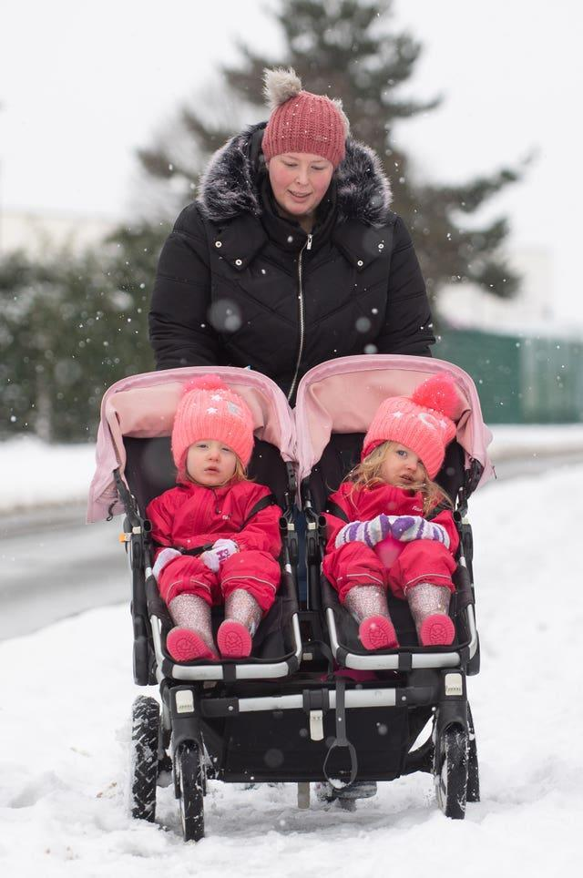 A mother pushes her twins through the snow in their buggy
