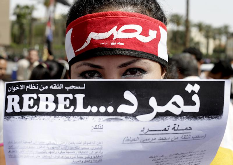 """FILE - In this Friday, May 17, 2013 file photo, An Egyptian activist covers her face with an applications for """"Tamarod"""", Arabic for """"rebel"""", a campaign calling for the ouster of Egyptian President Mohammed Morsi and for early presidential elections, during a protest in Tahrir Square, in Cairo, Egypt. Opponents of Egypt's Islamist president are convinced that nationwide protests planned for June 30 are their last opportunity to drive him from power. They say they have tapped into widespread public discontent over shortages, broken infrastructure, high prices and lack of security, and can bring that anger into the streets. (AP Photo/Hassan Ammar, File)"""