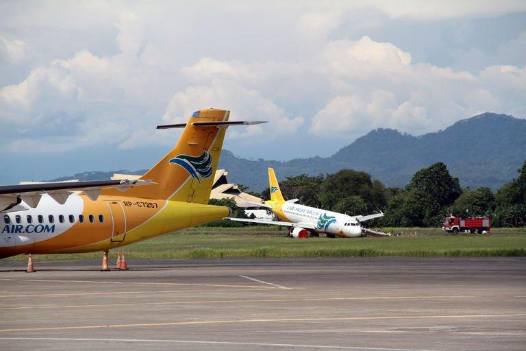 A Cebu Pacific Airbus A320 plane sits on the grassy part of the runway in Davao, Mindanao island, on June 3, 2013