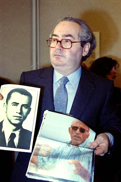 Nazi hunter Serge Klarsfeld holds up two pictures of war criminal Alois Brunner, in Paris in 1989 (AFP Photo/DANIEL JANIN)
