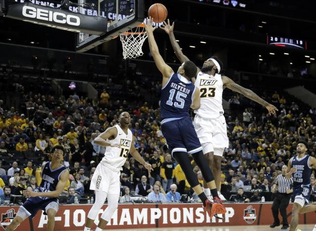 Rhode Island's Omar Silverio (15) drives past VCU's Issac Vann (23) during the second half of an NCAA college basketball game in the Atlantic 10 men's tournament Friday, March 15, 2019, in New York. Rhode Island won 75-70. (AP Photo/Frank Franklin II)