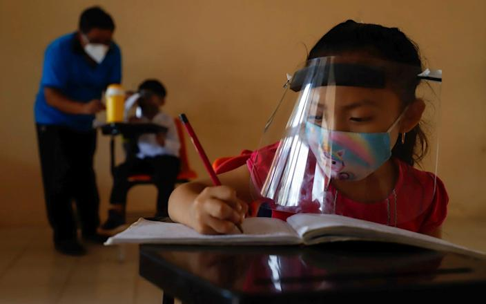 Wearing a mask and a face shield to curb the spread of the new coronavirus, 10-year-old Jade Chan Puc writes in her notebook during the first day of class in Montebello, Campeche state - the first region to transition back to the classroom after a year of remote learning due to the pandemic - AP Photo/Martin Zetina