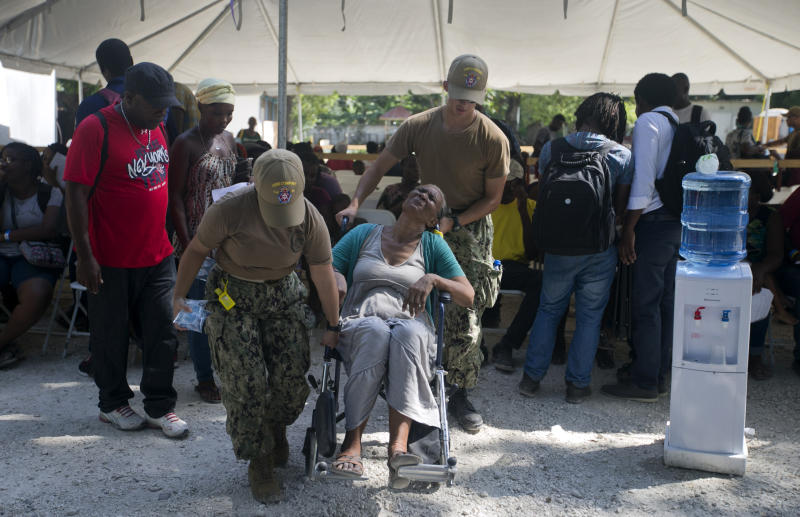 U.S. soldiers move an elderly Haitian woman in a wheelchair to see a U.S. military doctor from the US Navy hospital ship USNS Comfort anchored off Port-au-Prince, Haiti, Friday, Nov. 8, 2019. The visit of the hospital ship comes as violent demonstrations and street barricades have led several hospitals across the country to run out of medical supplies and some have temporarily closed as protesters keep demanding the president's resignation. (AP Photo/Dieu Nalio Chery)