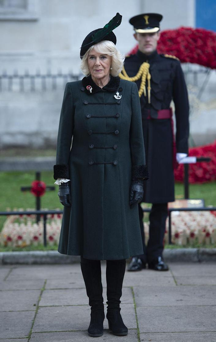 <p>Camilla, Duchess of Cornwall, wore an emerald and black fur-trimmed coat and black leather gloves while attending the 92nd Field of Remembrance at Westminster Abbey. She topped off the look with a black hat embellished with a feather.</p>