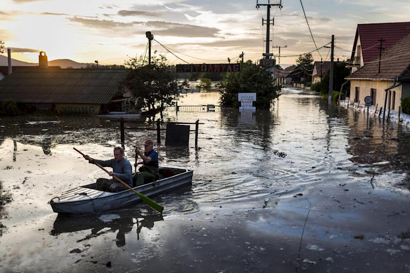 Two men paddle in the flooded water of River Danube after a temporary dam was broken in Tahitotfalu, 30 kms north of Budapest, Hungary, Saturday, June 8, 2013. (AP Photo/MTI, Balazs Mohai)